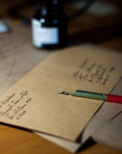 image of pen resting on an envelope as if it has just been addressed