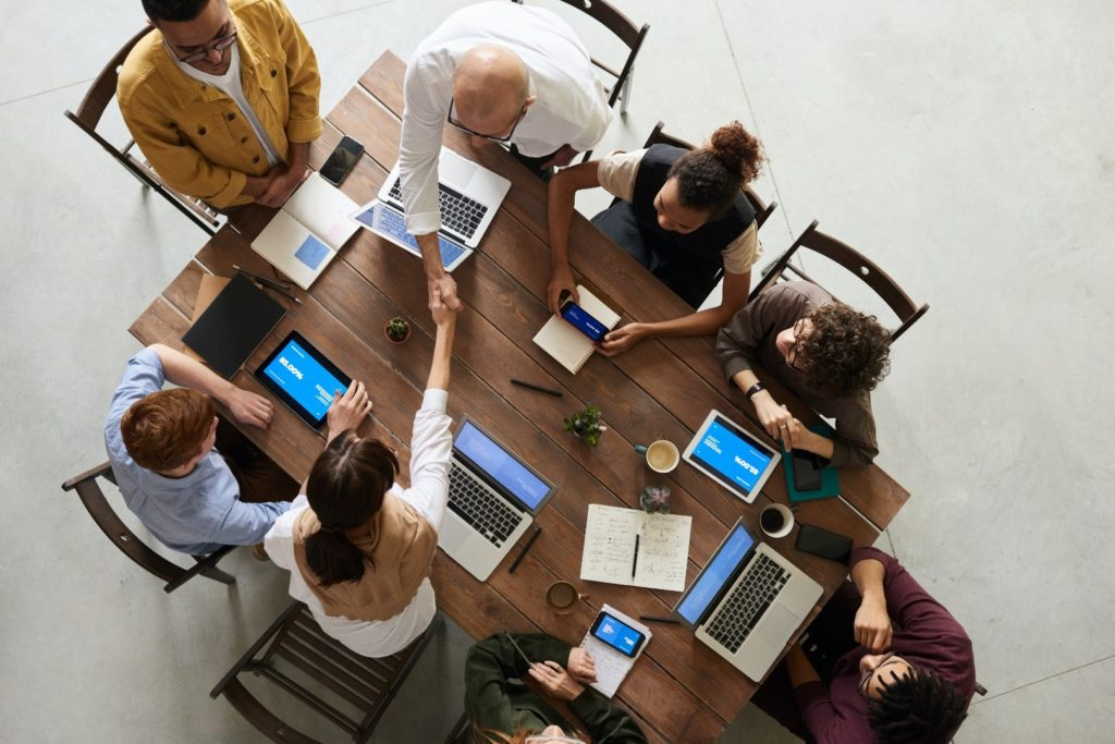 A group of professionals at a meeting table with a variety of devices open in front of them